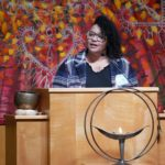 Kyana Wheeler stands behind a lecturn with a lit UU Chalice in the foregound; she looks out and speaks to the audience.