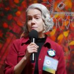 Holding a microphone in hand, Cynthia Good looks out at the audience quizically.