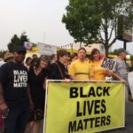 More than 20 adults stand proudly behind a 6 foot Black Lives Matters banner on a street corner