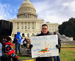 Native man outside capitol building holding sign supporting Mashpee
